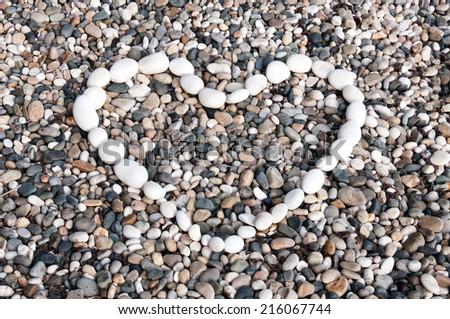 Pebble heart on the beach - stock photo