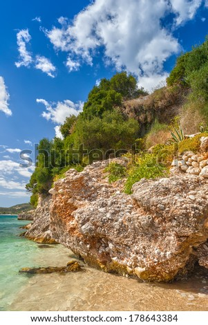 Pebble rock formation under bright sunlight at the shore of Ionian sea, Corfu, Greece - stock photo