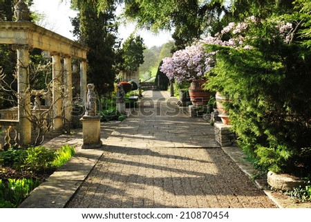 Pebble Walkway in a Beautiful Landscape Garden Bathed in Warm Evening Sun - stock photo
