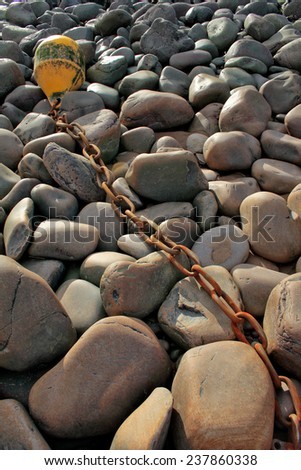 Pebbles and rocks and a buoy on a beach in Somerset, England, UK.