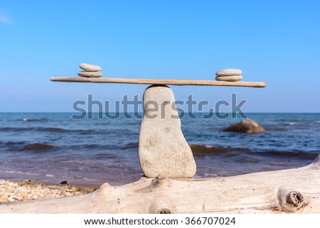 Pebbles in balance on the narrow plank - stock photo
