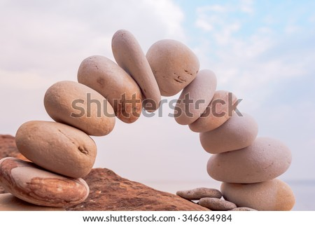 Pebbles in the form of a arch on coast - stock photo