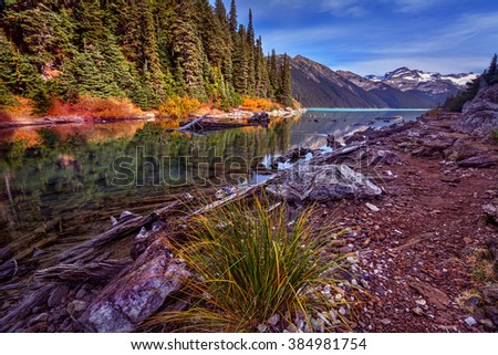 Pebbles on the mountain side pathway, revealing the snow-capped mountain afar, dense trees and clear water revealing wood at the bottom - stock photo