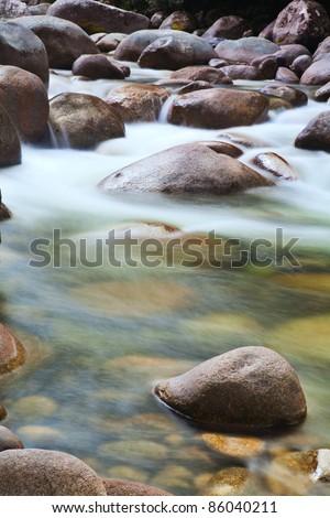 pebbles or rocks in creek or stream flowing water - stock photo