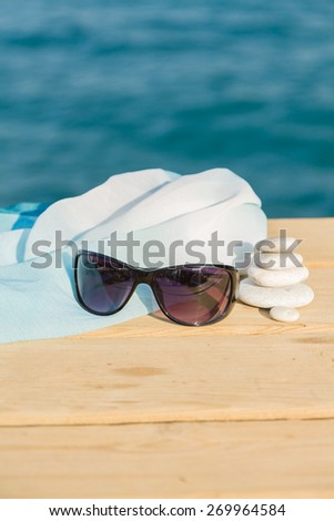 Pebbles stack and sunglasses on the wood pier balance over sea - stock photo