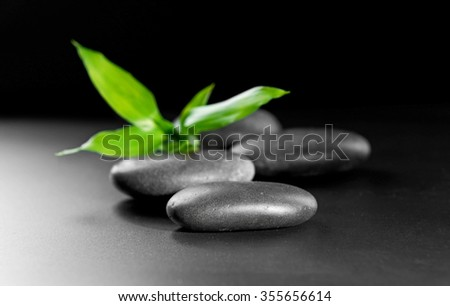 Pebbles with bamboo leaf on black background - stock photo