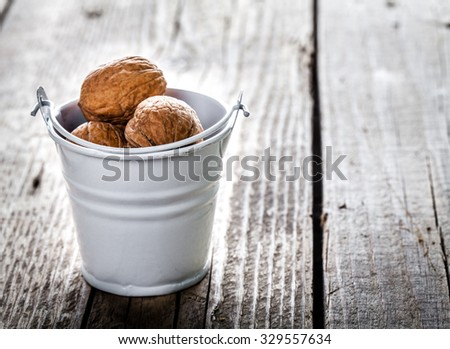pecan nuts in a bucket on a wooden background - stock photo
