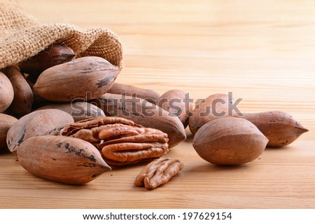 Pecan nuts in a burlap sack bag close up on a wooden background