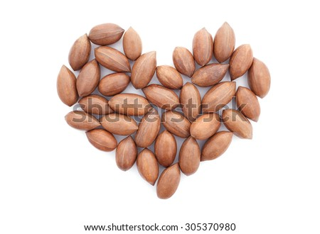 Pecan nuts in a heart shape, isolated on a white background - stock photo