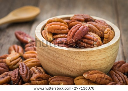 Pecan nuts in wooden bowl - stock photo