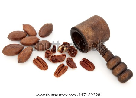 Pecan nuts with an old wooden nutcracker over white background