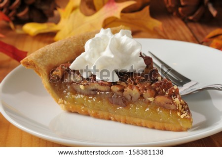 Pecan pie topped with whipped cream on a colorful holiday table - stock photo