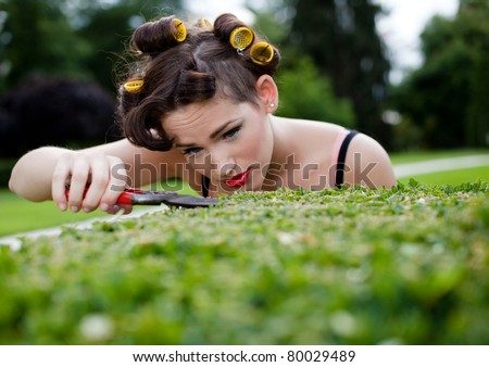 Pedantic housewife gardening. She's trimming the bush to perfection. Selective focus. - stock photo
