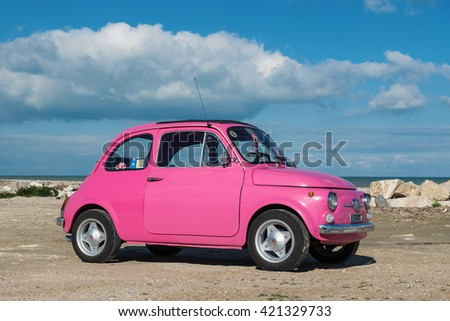 PEDASO, ITALY - FEBRUARY 20, 2016: Old pink Fiat Nuova 500 city car parked close to the sea with cloudy blue sky. Produced by the Italian manufacturer Fiat between 1957 and 1975.