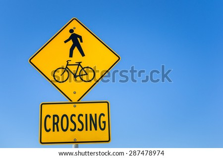 Pedestrian and bicycle Path Crossing Traffic Sign against Blue Sky. - stock photo