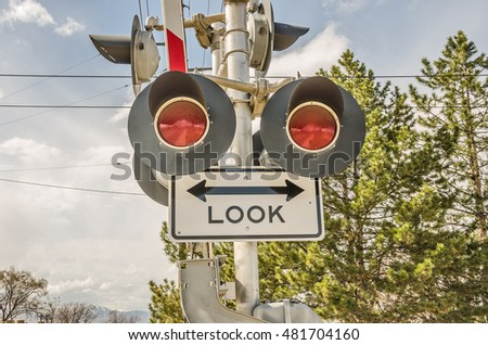 Pedestrian and vehicle signal at a crossing for high speed commuter trains warning people to look before crossing and to stop when red lights are flashing