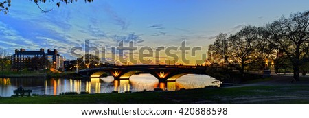 Pedestrian bridge across Charles River in Cambridge, Massachusetts. Panoramic view at dusk. - stock photo