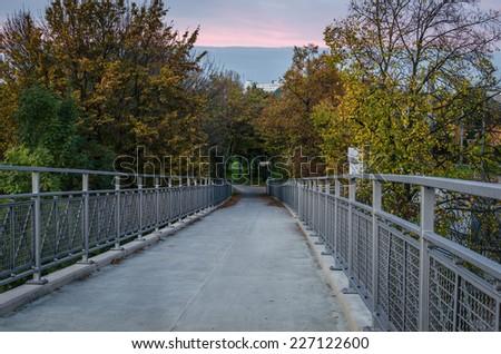 Pedestrian bridge at sunset - stock photo