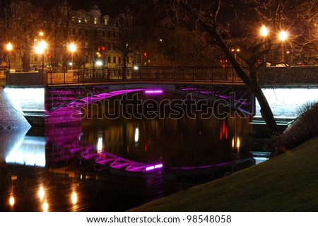 Pedestrian bridge over Riga channel by night. Latvia - stock photo