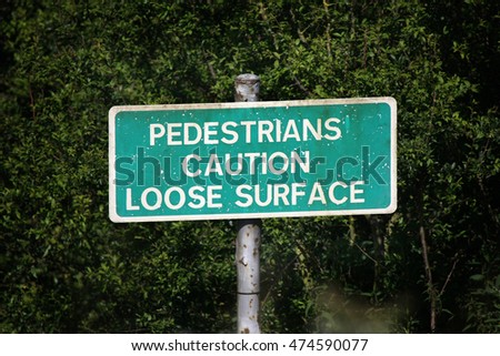Pedestrian caution sign on footpath for loose surface.