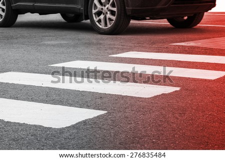 Pedestrian crossing road marking and moving car, photo with red gradient tonal filter, selective focus and shallow DOF - stock photo