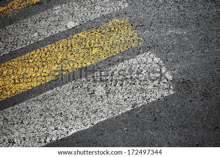 Pedestrian crossing road marking on dirty asphalt pavement - stock photo