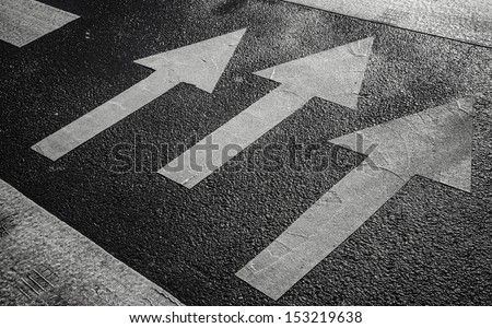 Pedestrian crossing road marking with white arrows on asphalt - stock photo