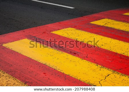 Pedestrian crossing road marking with yellow and red lines on asphalt