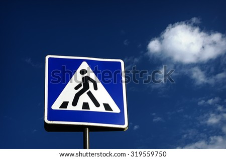 Pedestrian crossing sign against blue sky with white clouds - stock photo
