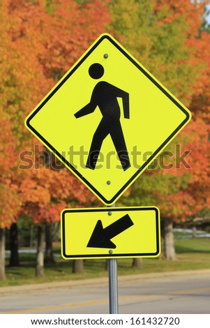 Pedestrian crossing sign against red maple trees