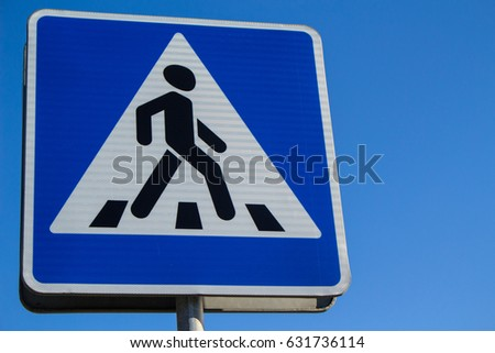 Pedestrian crossing sign against the blue sky