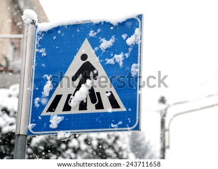 pedestrian crossing sign in mountain village during heavy snowstorm - stock photo