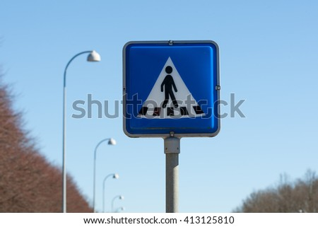 pedestrian crossing sign with blue sky and trees in background - stock photo