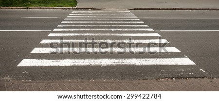 Pedestrian crossing white lines on the narrow asphalt road - stock photo