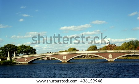 Pedestrian Harvard Bridge in Boston Massachusetts on Charles river with Harvard Campus in the background on a sunny day with blue sky - stock photo