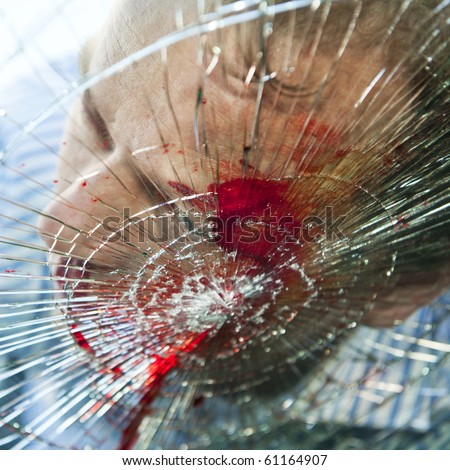 Pedestrian hit by a car, with blood on the splintered windshield - stock photo
