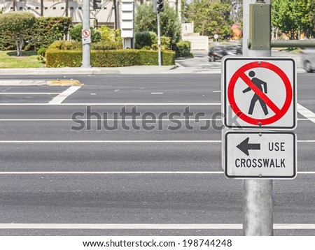 Pedestrian no entry sign on wide urban street. No crossing icon mounted on metal pole. Instructions with words and arrow to use crosswalk for safety.   - stock photo