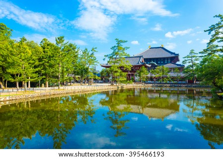 Pedestrian path and tranquil lake reflecting the front red entrance gate to Daibutsuden seen in distance on beautiful, sunny blue sky morning at Todai-ji temple in Nara, Japan. Horizontal copy space