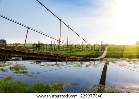 Pedestrian suspension bridge of steel and wood over the river, summer in Russia
