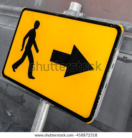 Pedestrians bypass direction. Yellow road sign close-up photo