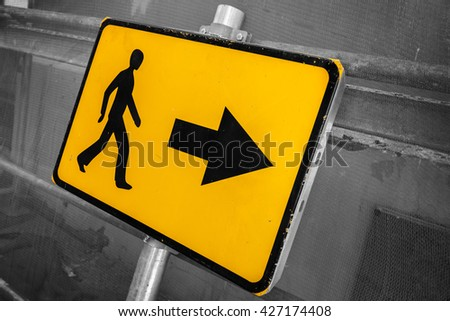 Pedestrians bypass direction. Yellow road sign on construction site fence - stock photo