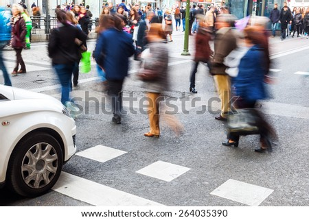 pedestrians in motion blur crossing a city street while car is waiting - stock photo