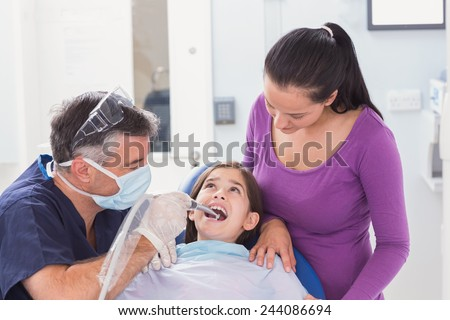Pediatric dentist examining young patient with her mother in dental clinic - stock photo