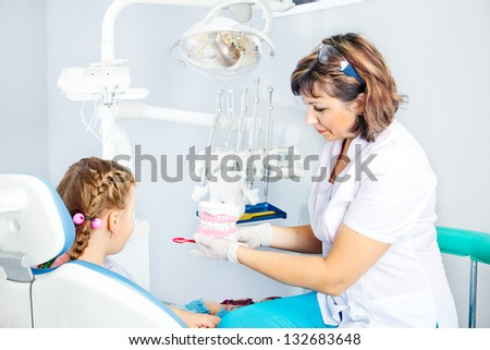 Pediatric dentist showing artificial toy denture - stock photo