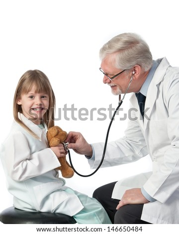 Pediatric doctor cares for a young female patient with stethoscope on teddy bear - stock photo