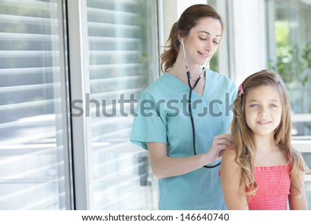 pediatrician checking her patient - stock photo