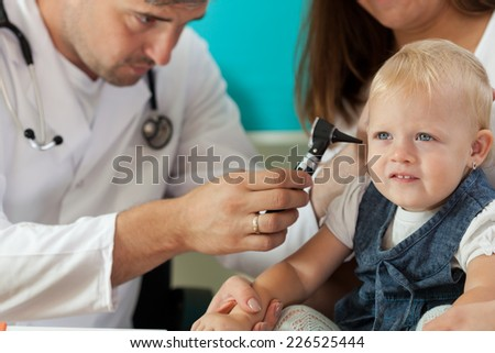 Pediatrician checking little girl ears by otoscope