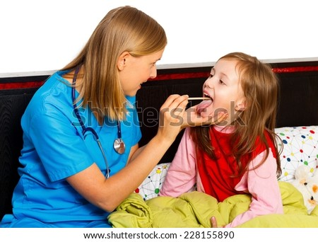 Pediatrician checking little patient's throat with wooden pile. - stock photo