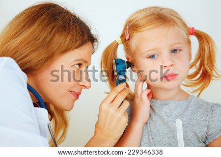 Pediatrician doctor examining little girl's ears. - stock photo