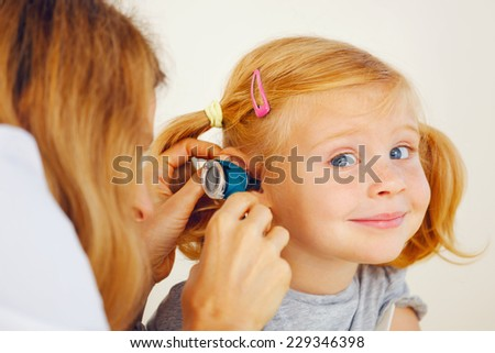 Pediatrician doctor examining little girl`s ears. - stock photo